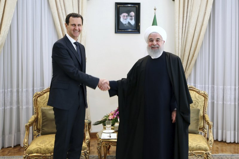 FILE - In this February 25, 2019 file photo, released by an official website of the office of the Iranian Presidency, President Hassan Rouhani, right, shakes hands with Syrian President Bashar Assad before their meeting at his office in Tehran, Iran. (Office of the Iranian Supreme Leader via AP, File)