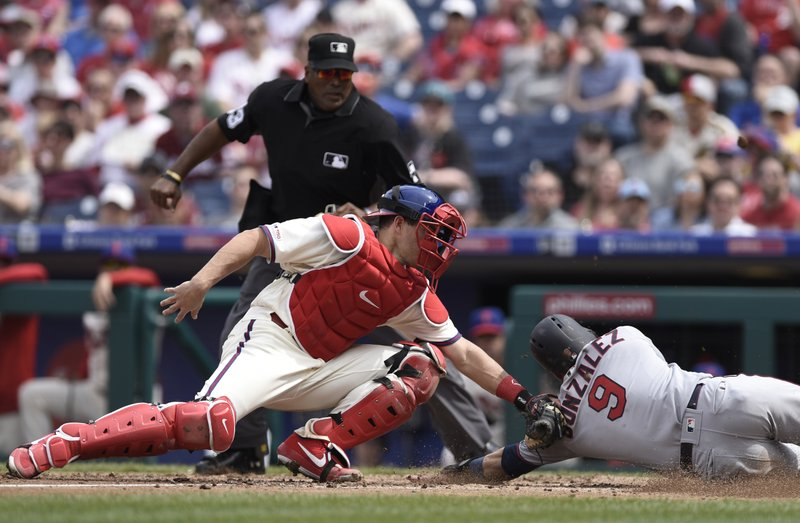 Minnesota Twins' Marwin Gonzalez, right, is tagged out at home plate by Philadelphia Phillies' J.T. Realmuto during the fourth inning of a baseball game Sunday, April 7, 2019, in Philadelphia. (AP Photo/Michael Perez)