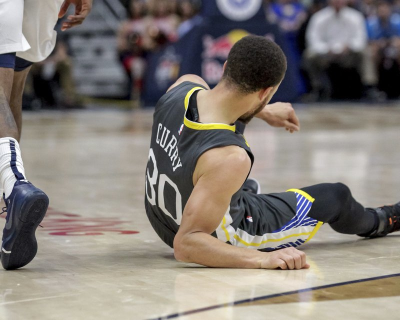 Golden State Warriors guard Stephen Curry (30) goes to the court after twisting his ankle in the first half of an NBA basketball game in New Orleans, Tuesday, April 9, 2019. (AP Photo/Scott Threlkeld)