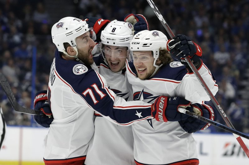 Columbus Blue Jackets defenseman Zach Werenski (8) celebrates his goal against the Tampa Bay Lightning with left wing Nick Foligno (71) and left wing Artemi Panarin (9) during the first period of Game 2 of an NHL Eastern Conference first-round hockey playoff series Friday, April 12, 2019, in Tampa, Fla. (AP Photo/Chris O'Meara)