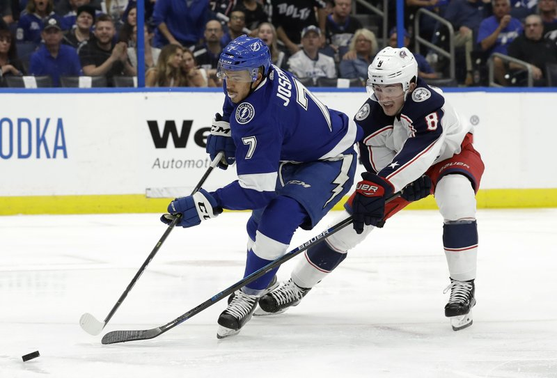 Tampa Bay Lightning right wing Mathieu Joseph (7) gets around Columbus Blue Jackets defenseman Zach Werenski (8) during the second period of Game 2 of an NHL Eastern Conference first-round hockey playoff series Friday, April 12, 2019, in Tampa, Fla. (AP Photo/Chris O'Meara)