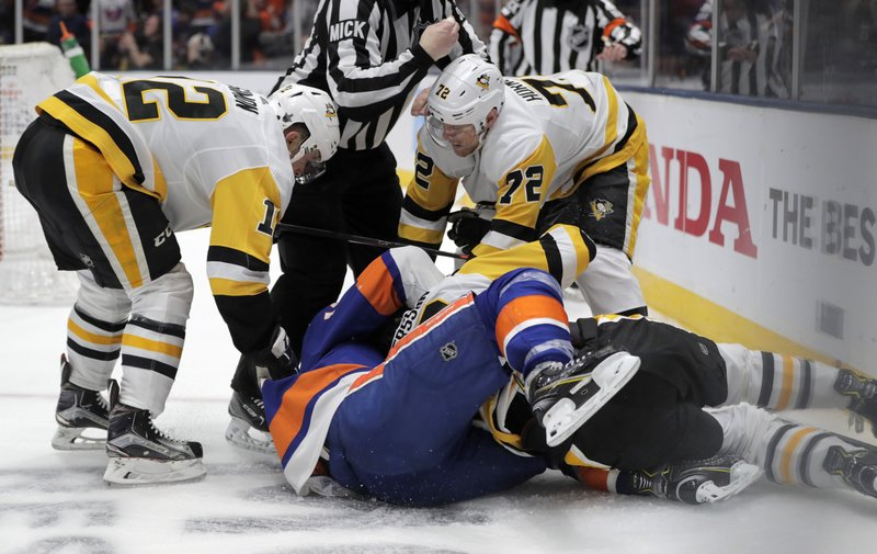 Pittsburgh Penguins center Dominik Simon (12), of the Czech Republic, and right wing Patric Hornqvist (72), of Sweden, pile on as defenseman Marcus Pettersson, bottom right, of Sweden, fights with  New York Islanders center Mathew Barzal seconds after the Islanders scored a goal during the second period of Game 2 of an NHL hockey first-round playoff series Friday, April 12, 2019, in Uniondale, N. (AP Photo/Julio Cortez)