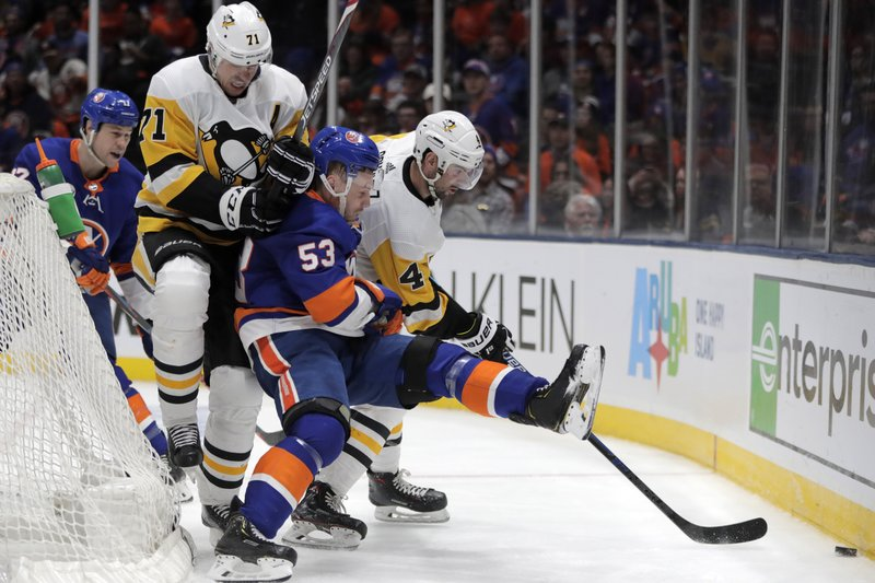 New York Islanders center Casey Cizikas (53) is sandwiched between Pittsburgh Penguins center Evgeni Malkin (71), of Russia, and defenseman Justin Schultz (4) while competing for possession of the puck during the second period of Game 2 of an NHL hockey first-round playoff series Friday, April 12, 2019, in Uniondale, N. (AP Photo/Julio Cortez)