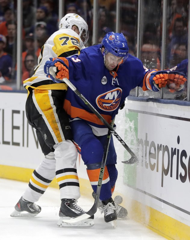 Pittsburgh Penguins right wing Patric Hornqvist (72), of Sweden, and New York Islanders defenseman Adam Pelech (3) compete for possession during the first period of Game 2 of an NHL hockey first-round playoff series Friday, April 12, 2019, in Uniondale, N. (AP Photo/Julio Cortez)