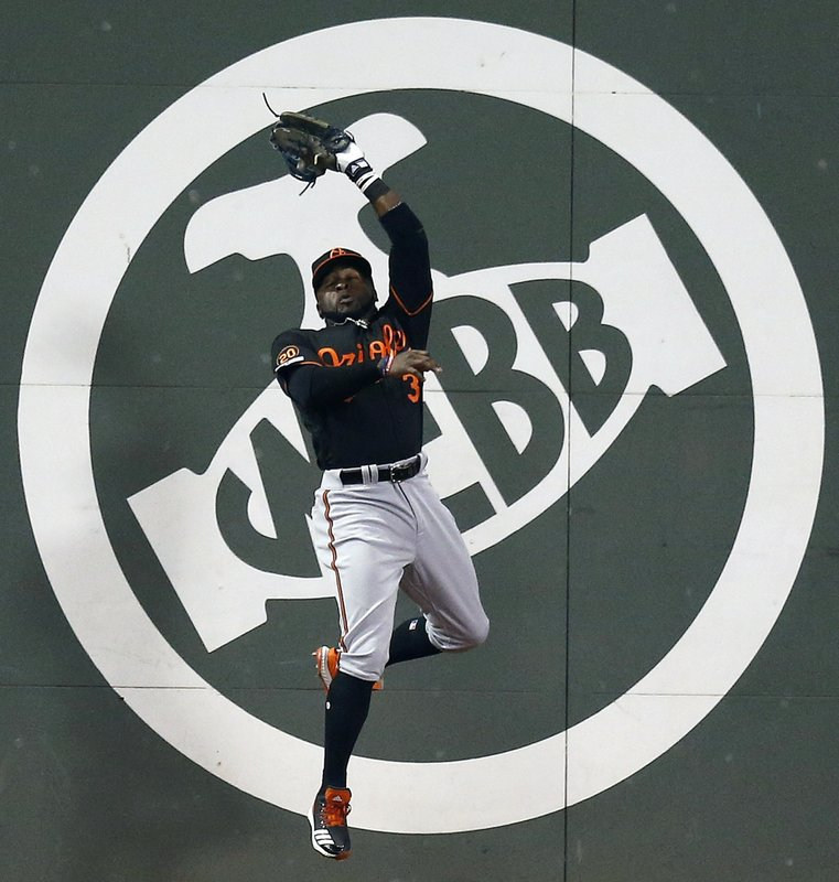 Baltimore Orioles' Dwight Smith Jr. makes the catch on a fly-out by Boston Red Sox's J.D. Martinez during the fourth inning of a baseball game in Boston, Friday, April, 12, 2019. (AP Photo/Michael Dwyer)
