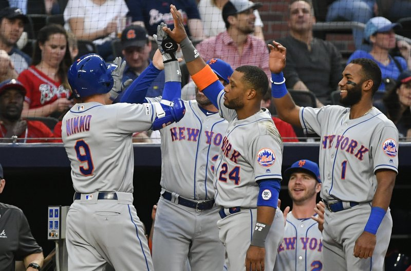 New York Mets' Brandon Nimmo (9) is congratulated by Robinson Cano (24) and Amed Rosario (1) as he enters the dugout after hitting a two-run home run during the second inning of a baseball game against the Atlanta Braves, Friday, April 12, 2019, in Atlanta. (AP Photo/John Amis)
