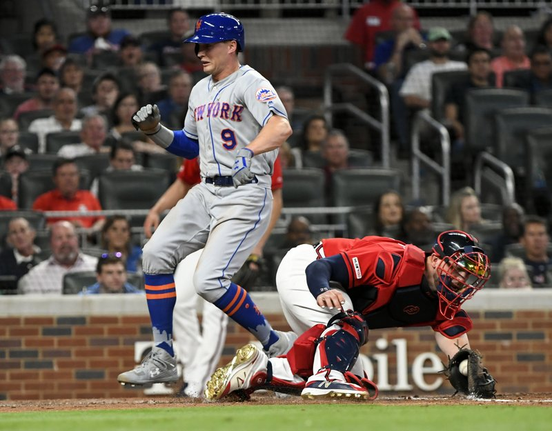 New York Mets' Brandon Nimmo (9) crosses home plate behind Atlanta Braves catcher Tyler Flowers, on a Jeff McNeil two-run double to right field during the fourth inning of a baseball game Friday, April 12, 2019, in Atlanta. (AP Photo/John Amis)