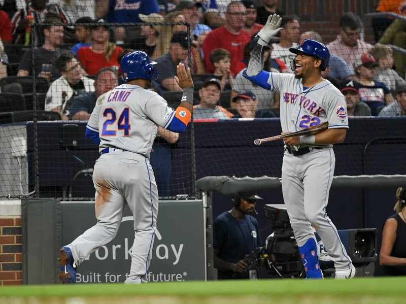 New York Mets Dominic Smith (22) celebrates as Robinson Cano comes to the dugout after scoring on a Michael Conforto double to right field during the fourth inning of a baseball game against the Atlanta Braves, Friday, April 12, 2019, in Atlanta. (AP Photo/John Amis)