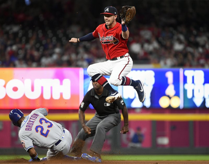 New York Mets' Keon Broxton (23) steals second base as Atlanta Braves shortstop Dansby Swanson goes high for the throw from catcher Tyler Flowers during the fourth inning of a baseball game Friday, April 12, 2019, in Atlanta. (AP Photo/John Amis)