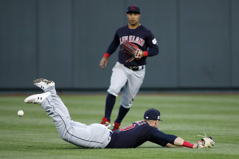 Cleveland Indians center fielder Leonys Martin, top, looks on as left fielder Jake Bauers, bottom, is unable to catch a short fly ball by Kansas City Royals batter Hunter Dozier in the first inning of a baseball game at Kauffman Stadium in Kansas City, Mo. (AP Photo/Colin E. Braley)