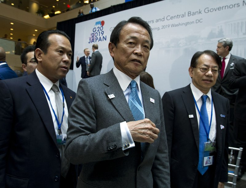 Japan's Finance Minister Taro Aso, center, leaves after the group photo of the G20 Finance Minister and Central Bank Governors at the World Bank/IMF Spring Meetings in Washington, Friday, April 12, 2019. (AP Photo/Jose Luis Magana)