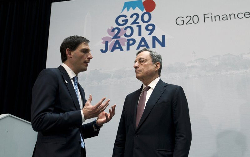 Netherlands' Finance Minister Wopke Hoekstra, left, speaks with the President of European Central Bank Mario Draghi, during a group photo of the G20 Finance Minister and Central Bank Governors at the World Bank/IMF Spring Meetings in Washington, Friday, April 12, 2019. (AP Photo/Jose Luis Magana)