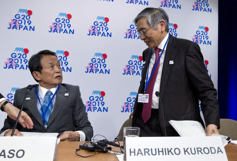 Japan's Finance Minister Taro Aso, left, accompanied by Bank of Japan Governor Haruhiko Kuroda, leave after speaking at G20 news conference, during the World Bank/IMF Spring Meetings in Washington, Friday, April 12, 2019. (AP Photo/Jose Luis Magana)