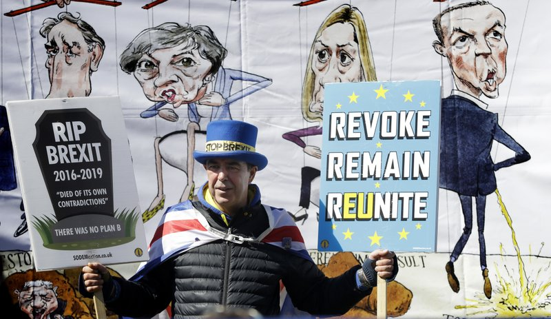 Anti-Brexit demonstrator Steve Bray stands in front of a banner held by pro-Brexit demonstrators near Parliament in London, Wednesday, April 10, 2019. (AP Photo/Kirsty Wigglesworth)