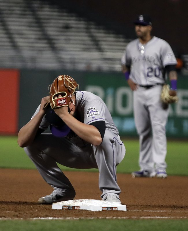 Colorado Rockies' DJ Johnson holds his glove to his head at the end of an 18 inning baseball game against the San Francisco Giants Saturday, April 13, 2019, in San Francisco. (AP Photo/Ben Margot)