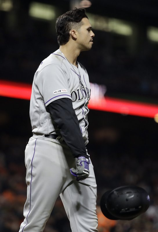 Colorado Rockies' Josh Fuentes throws his helmet after striking out to San Francisco Giants' Tony Watson with the bases loaded in the eighth inning of a baseball game Friday, April 12, 2019, in San Francisco. (AP Photo/Ben Margot)