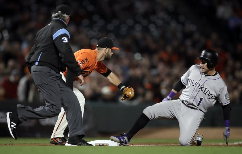 Colorado Rockies' Garrett Hampson, right, beats the tag of San Francisco Giants third baseman Evan Longoria for a triple during the fourth inning of a baseball game Friday, April 12, 2019, in San Francisco. (AP Photo/Ben Margot)