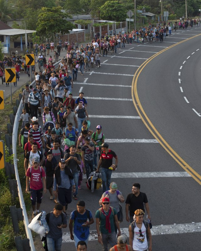 CORRECTS LOCATION - Central American migrants, part of a caravan hoping to reach the U.S. border, walk on the shoulder of a road in Frontera Hidalgo, Mexico, Friday, April 12, 2019. (AP Photo/Isabel Mateos)
