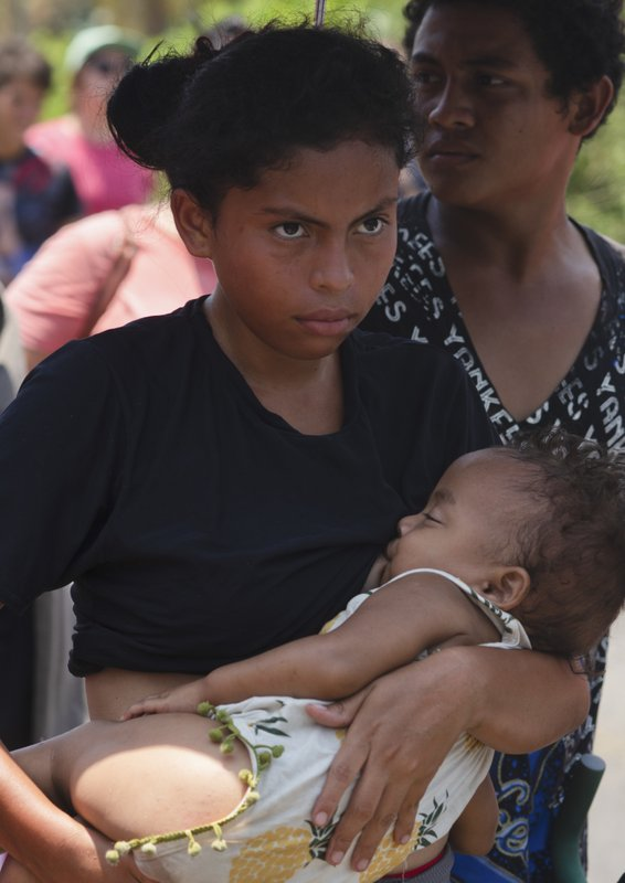A migrant mother breastfeeds her child as she walks with members of a caravan hoping to reach the U.S. (AP Photo/Isabel Mateos)