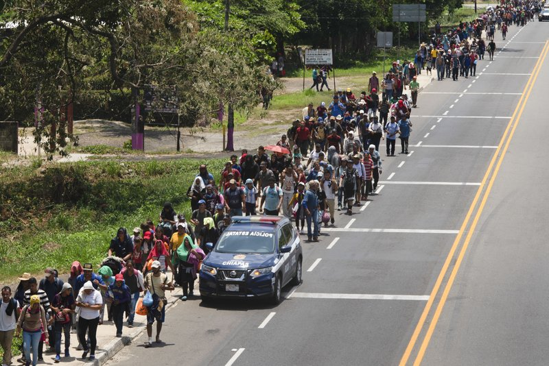 Central American migrants, part of a caravan hoping to reach the U.S. border, walk on the shoulder of a road in Frontera Hidalgo, Mexico, Friday, April 12, 2019. (AP Photo/Isabel Mateos)