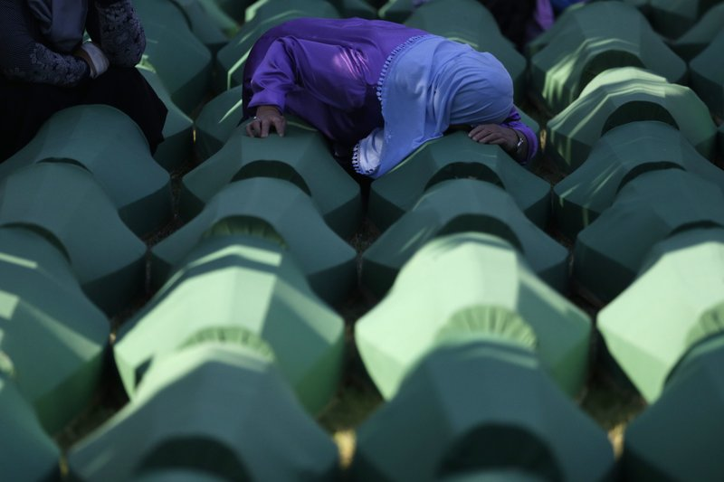 FILE - In this Monday, July 11, 2016 file photo, a Bosnian woman prays next to a coffin containing the remains of her relative perished in the Srebrenica massacre, during a funeral ceremony for the 127 victims at the Potocari memorial complex near Srebrenica, 150 kilometers (94 miles) northeast of Sarajevo, Bosnia and Herzegovina. (AP Photo/Amel Emric, File)