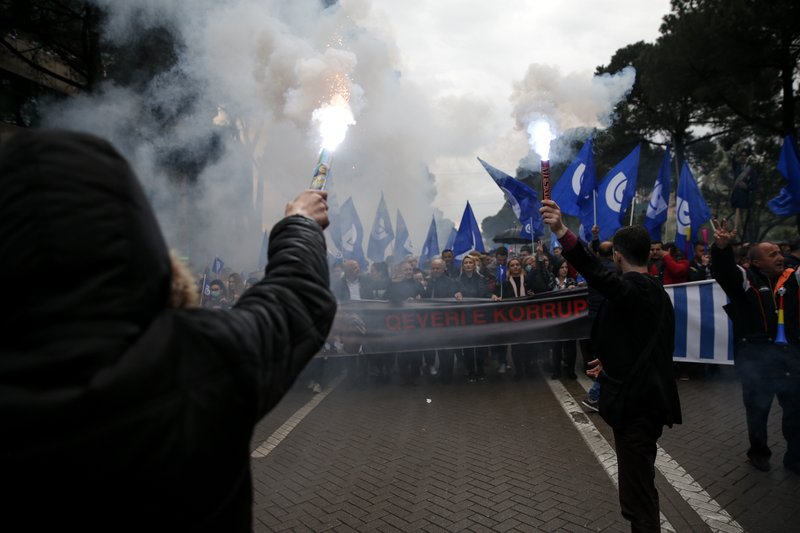 Protester hold flares as they take part in an anti-government protest in the capital Tirana, Saturday, April 13, 2019. (AP Photo/Visar Kryeziu)
