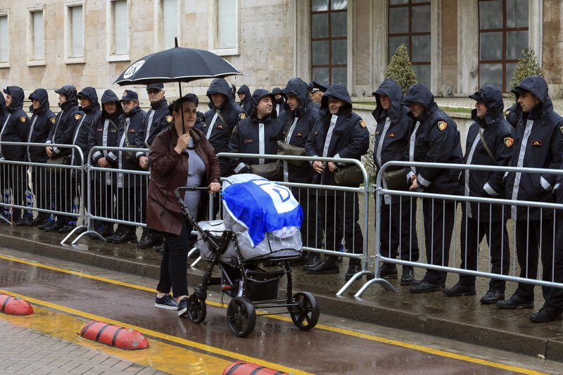 A woman pushes a baby stroller alongside a police formation ahead of an anti-government protest in the capital Tirana, Saturday, April 13, 2019. (AP Photo/Hektor Pustina)