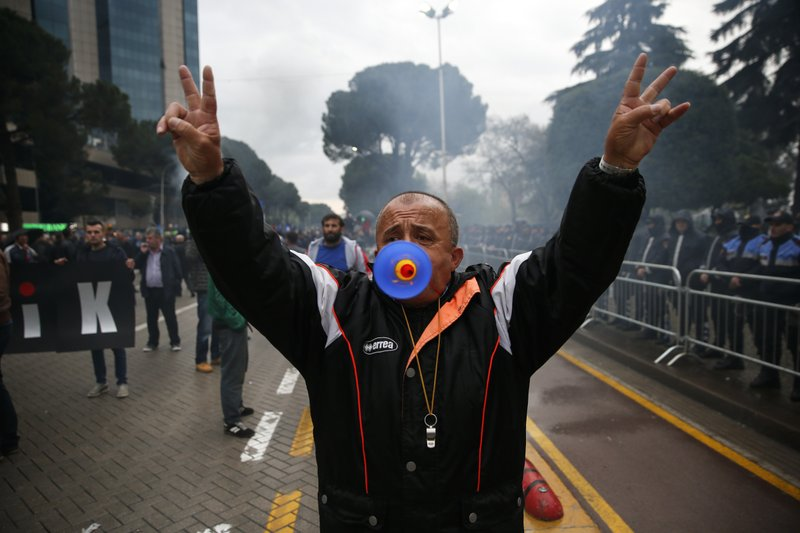 A protester blows a horn as he gestures, during an anti-government protest in the capital Tirana, Saturday, April 13, 2019. (AP Photo/Visar Kryeziu)