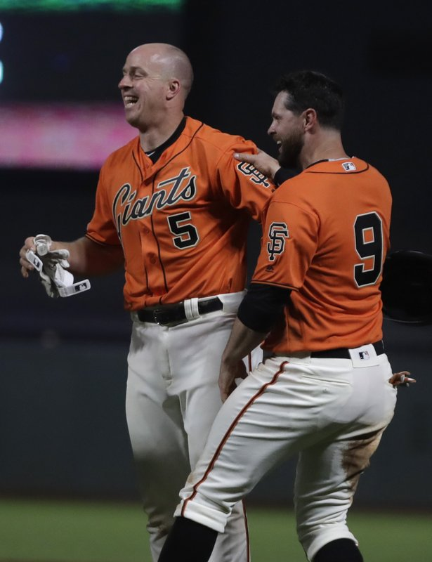 San Francisco Giants' Erik Kratz (5) and Brandon Belt, right, celebrate at the end of an 18 inning baseball game against the Colorado Rockies Saturday, April 13, 2019, in San Francisco. (AP Photo/Ben Margot)