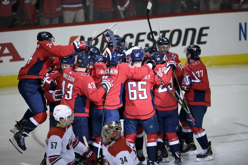The Washington Capitals celebrate after overtime of Game 2 of an NHL hockey first-round playoff series as Carolina Hurricanes defenseman Trevor van Riemsdyk (57) and goaltender Petr Mrazek (34) skate by, Saturday, April 13, 2019, in Washington. (AP Photo/Nick Wass)