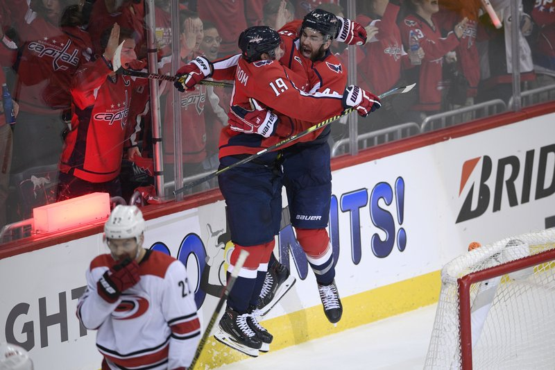 Washington Capitals right wing Tom Wilson (43) celebrates his goal with center Nicklas Backstrom (19), of Sweden, during the third period of Game 2 of an NHL hockey first-round playoff series as Carolina Hurricanes defenseman Brett Pesce (22) skates away, Saturday, April 13, 2019, in Washington. (AP Photo/Nick Wass)