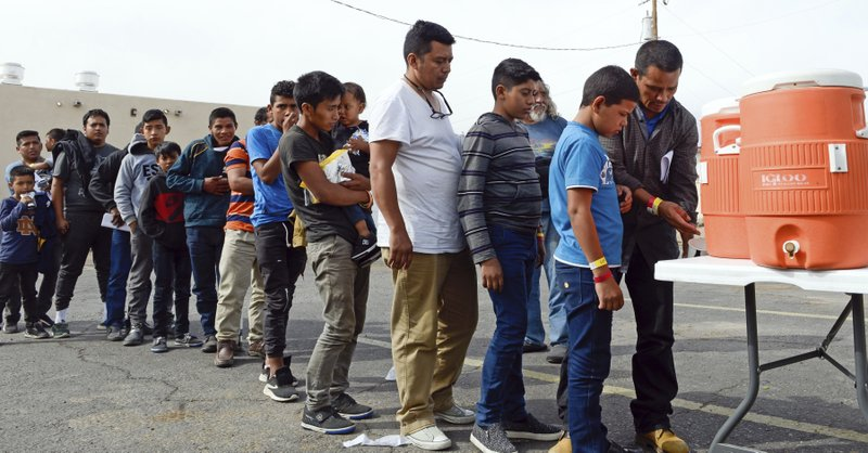 In this Friday, April 12, 2019 photo, migrants wait in line to get drinks after being dropped off by the Border Patrol at the Gospel Rescue Mission in Las Cruces, N. (Blake Gumprecht/The Las Cruces Sun News via AP)