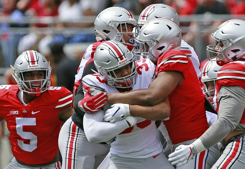 Ohio State's Master Teague III is tackled by Tyreke Smith (11) during the spring NCAA college football game at the Ohio Stadium in Columbus, Ohio, Saturday April 13, 2019. (Brooke LaValley/The Columbus Dispatch via AP)