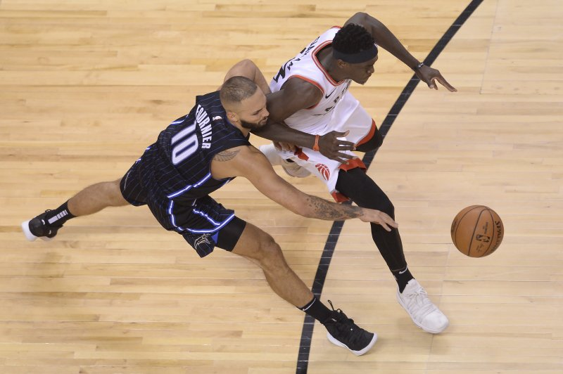 Toronto Raptors forward Pascal Siakam (43) steals the ball from Orlando Magic guard Evan Fournier (10) and then scores on a dunk during the second half in Game 1 of a first-round NBA basketball playoff series in Toronto, Saturday, April 13, 2019. (Nathan Denette/The Canadian Press via AP)