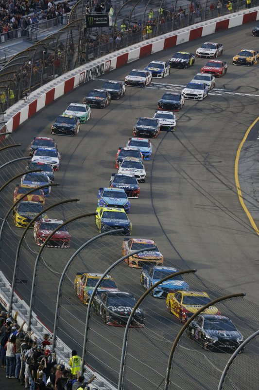 Kevin Harvick, lower right, leads the field at the start of the NASCAR Cup series auto race at Richmond Raceway in Richmond, Va. (AP Photo/Steve Helber)