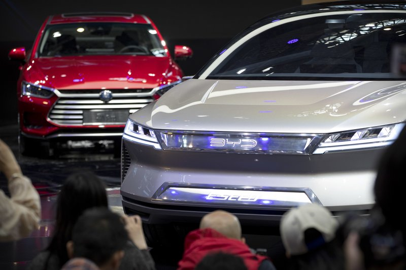FILE - In this April 25, 2018, file photo, attendees take photos of the E-SEED electric concept car during a press conference by Chinese automaker BYD at the China Auto Show in Beijing. (AP Photo/Mark Schiefelbein, File)
