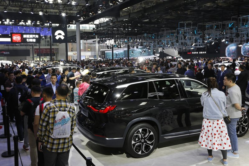 FILE - In this April 29, 2018, file photo, visitors watch an electric-powered SUV manufactured by Chinese automaker NIO during the China Auto Show in Beijing. (AP Photo/Andy Wong, File)