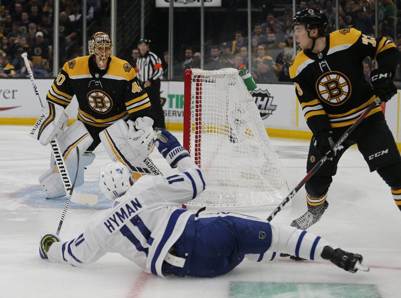 Toronto Maple Leafs left wing Zach Hyman (11) slides past the goal after losing his edge as Boston Bruins goaltender Tuukka Rask (40) and defenseman Charlie McAvoy (73) look on during the first period of Game 2 of an NHL hockey first-round playoff series, Saturday, April 13, 2019, in Boston. (AP Photo/Mary Schwalm)