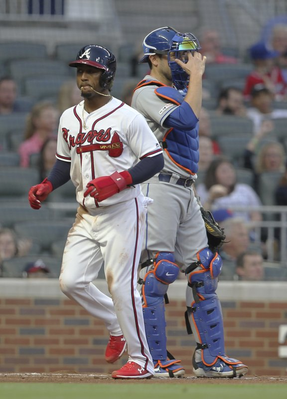 Atlanta Braves' Ozzie Albies, left, scores past New York Mets catcher Travis d'Arnaud during the first inning of a baseball game Saturday, April 13, 2019, in Atlanta. (AP Photo/Tami Chappell)