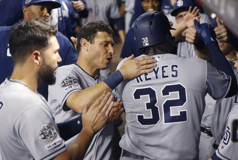 San Diego Padres' Franmil Reyes (32) celebrates his home run against the Arizona Diamondbacks with teammates Eric Hosmer, left, and Ian Kinsler, second from left, during the seventh inning of a baseball game Saturday, April 13, 2019, in Phoenix. (AP Photo/Ross D. Franklin)