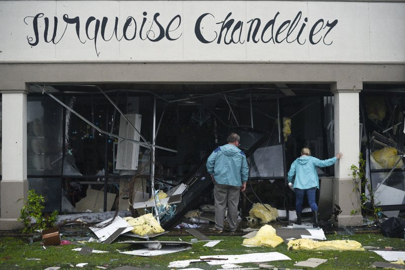 Robert and Marion Murphy peek into their damaged shop in the Pemberton Quarters strip mall following severe weather Saturday, April 13, 2019 in Vicksburg, Miss. (Courtland Wells/The Vicksburg Post via AP)