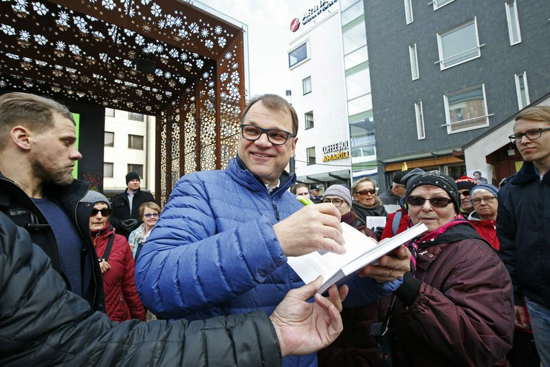 Chairman of the Centre Party and current Prime Minister Juha Sipila signs autographs as he campaigns for the Finnish parliamentary elections in Oulu, northern Finland, on Saturday, April 13, 2019. (Timo Heikkala/Lehtikuva via AP)