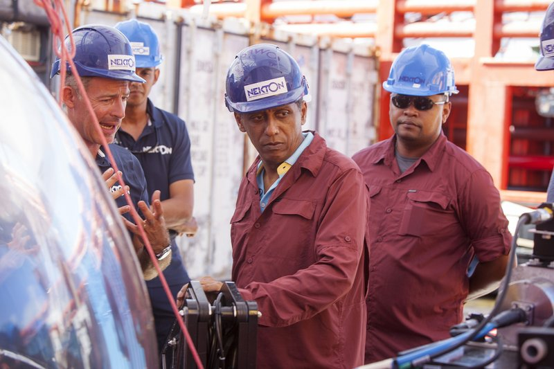 In this Saturday, April 13, 2019, photo, Seychelles President Danny Faure, center, gets briefed on the details of submersible operations on the deck of vessel Ocean Zephyr, off the coast of Desroches, in the outer islands of Seychelles. (AP Photo/Steve Barker)