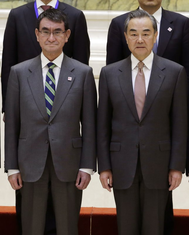Japanese Foreign Minister Taro Kono, left, and China's Foreign Minister Wang Yi attend a group photo event before the Japan-China high level economic dialogue at Diaoyutai State Guesthouse in Beijing, China, Sunday, April 14, 2019.(Jason Lee/Pool Photo via AP)