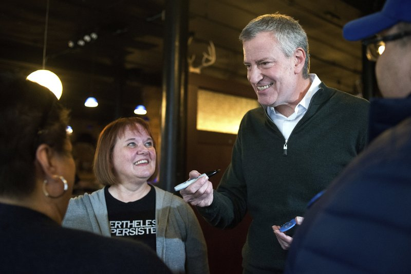 FILE - This Feb, 23, 2019 file photo shows New York City Mayor Bill de Blasio as he gives his autograph to Sandi O'Brien, left, of Sioux City, left, before an event hosted by the local Democratic party in Sioux City, Iowa. (Justin Wan/Sioux City Journal via AP, File)