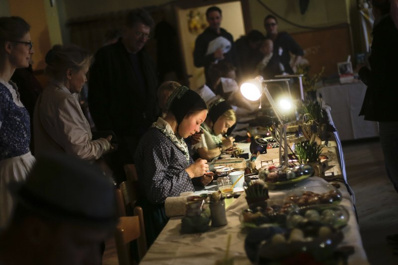 Thirteen years old Emelie Kaspar, center, decorates an Easter egg at a traditional Easter Market of Germany's Sorb minority in the village Neuwiese, near the city of Hoyerswerda in east Germany, Sunday, April 14, 2019. (AP Photo/Markus Schreiber)