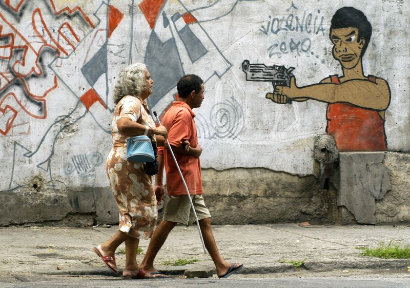FILE - In this Oct. 22, 2005 file photo, people walk past graffiti in Rio de Janeiro, Brazil, a day before a vote to ban the sale of firearms and ammunition to civilians. (AP Photo/Renzo Gostoli, File)