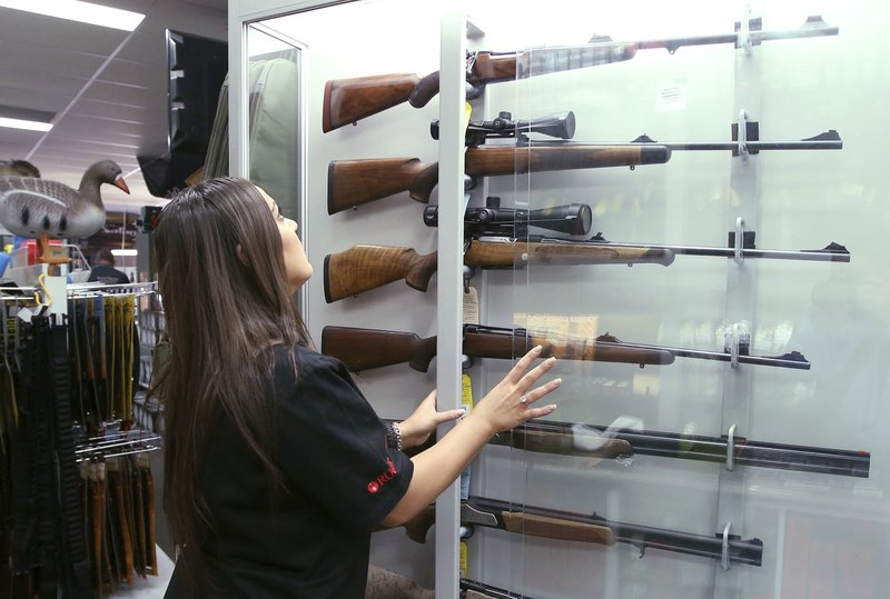 FILE - In this Wednesday, Oct. 4, 2017 file photo, a salesperson checks rifles in a gun shop display in Sydney, Australia. (AP Photo/Rick Rycroft)