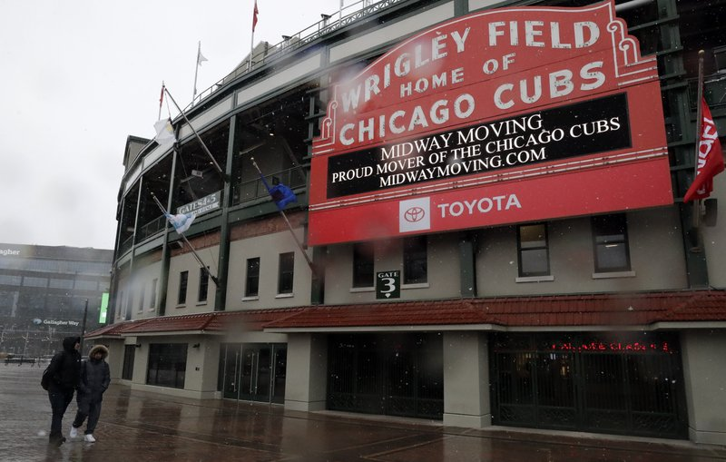 People walk in front of Wrigley Field, Sunday, April 14, 2019, in Chicago. The Chicago Cubs baseball game against the Los Angeles Angels was postponed due to inclement weather. (AP Photo/Nam Y. Huh)