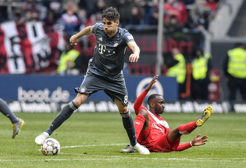 Bayern's Javi Martinez, left, and Duesseldorf's Dodi Lukebakio challenge for the ball during the German Bundesliga soccer match between Fortuna Duesseldorf and Bayern Munich in Duesseldorf, Germany, Sunday April 14, 2019. (AP Photo/Martin Meissner)